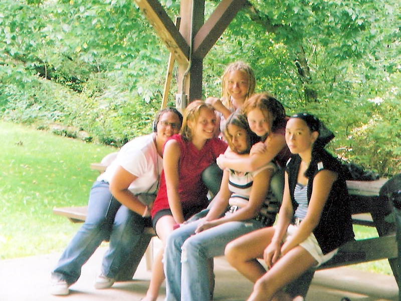 Smiling campers sitting on a picnic table outdoors