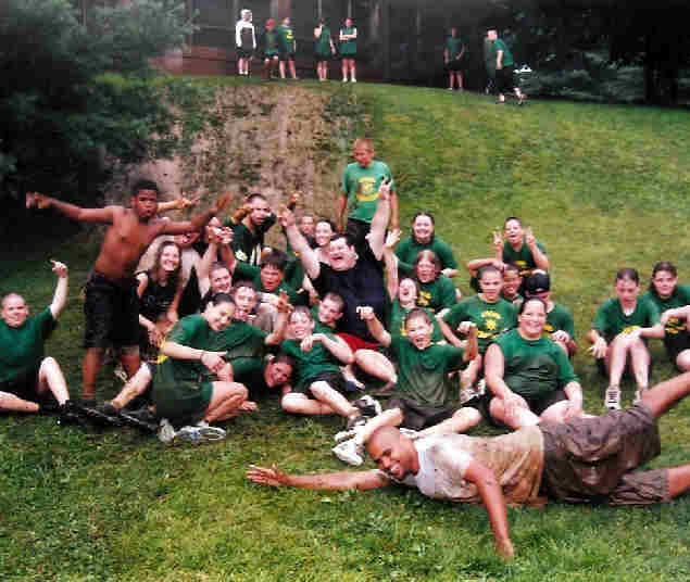Kids rolling down a muddy hill
