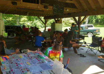 Kids sitting at picnic tables outside making crafts